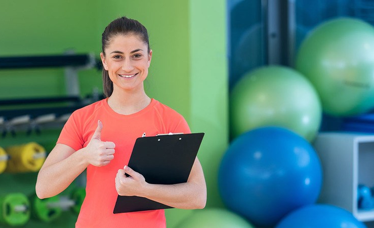 Portrait of smiling female fitness instructor writing in clipboard